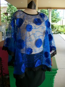 Blue sheer mesh with blue satin flowers, blue sequins and black lace trim. One size.
